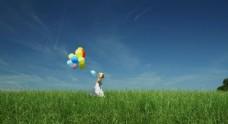 草地上小女孩拿气球跑过